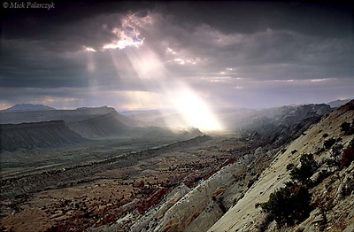 [USA.UTAH 28196 'Thunderstorm over the Waterpocket Fold.'  As a thunderstorm crosses Capitol Reef National Park, an isolated beam of light illuminates the Waterpocket Fold, a 65 million year old earthfold. The view is from Strike Overlook, looking south. Photo Mick Palarczyk.