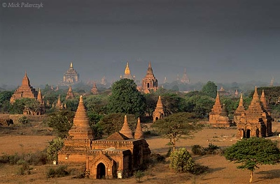 [BURMA 24.880] 'Bagan plain seen from Bulethi Stupa .'  The Bagan plain houses some two thousand temples and stupas. They are the 11th-13th century remnants of the now vanished royal city of Bagan. Here the plain is seen in the early morning from the Bulethi Stupa, looking west, with on the horizon the Thatbyinnyu Temple (left, with small golden spire) and the Ananda Temple (with big golden spire). Photo Mick Palarczyk.