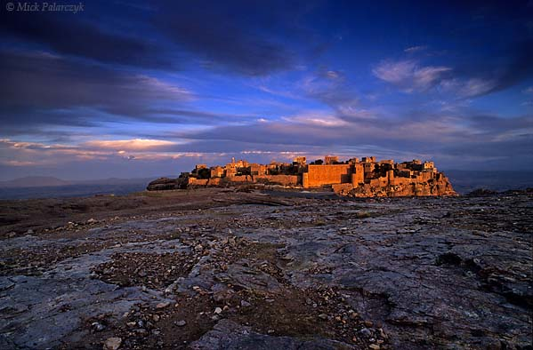 [YEMEN.NORTH 26502 'Kawkaban in last sunlight.'  The fortified town of Kawkaban catches the last rays of the setting sun. It is perched on the edge of a desolate plateau, 35 km west of Sana. Photo Mick Palarczyk.