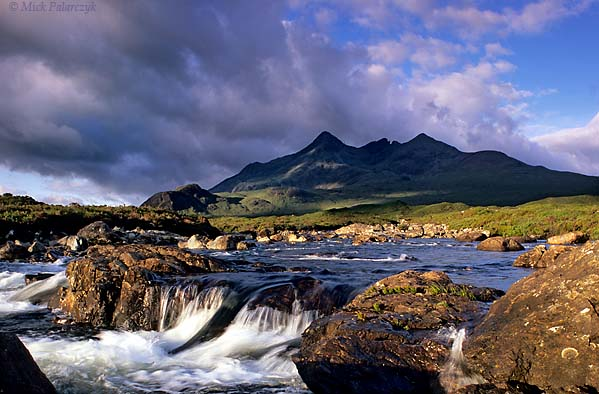[BRITAIN.HEBRIDES 27829] 'Sligachan River and Cuillins.'  Skye's Cuillins are considered the most impressive mountain range in the British Isles and a mecca for hikers and climbers. They are the remnants of large volcanoes which erupted when the Atlantic Ocean opened up and the American continent started  to drift away from Europe, 60 million years ago. The foreground of the picture shows the Sligachan River. Photo Mick Palarczyk.