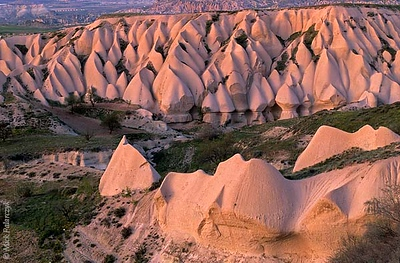 [TURKEY.CENTRAL 26858 'Eroded tuff near Uchisar.'  Erosion has turned these layers of volcanic tuff, north of the Cappadocian village of Uchisar, into a spectacular landscape of cones and curves. The slightly reddish hue of the tuff is exaggerated by the red glow of a setting sun. Photo Mick Palarczyk.