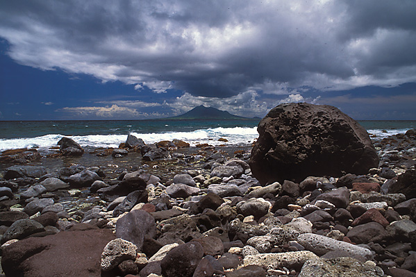 [ANTILLES.stEUSTATIUS 25.620] 'Corre Corre Bay.' Corre Corre Bay at the eastern tip of St.Eustatius is one of the loneliest spots on the island. Its coral laden beach seems just the spot to dig for a pirate treasure. Island-clouds formed in the rising air over St.Kitts are blown dramatically across the sky. Photo Mick Palarczyk.