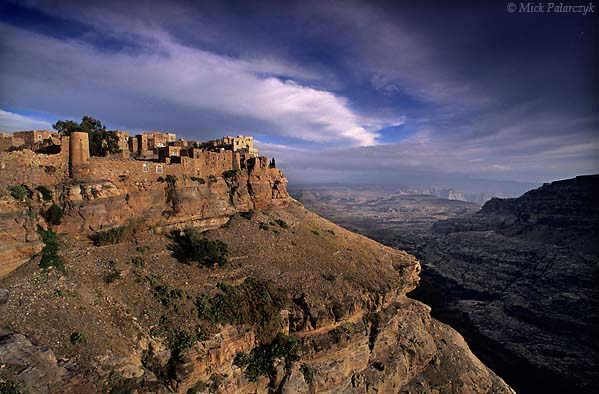 [YEMEN.NORTH 26495 'Kawkaban.'  The fortified town of Kawkaban is perched dramatically on the edge of a desolate plateau, 35 km west of Sana. When the region suffered raids by neighbouring tribes, Kawkaban served as a shelter for the citizens of its twin town Shibam which lies lower down on the plain. Photo Mick Palarczyk.
