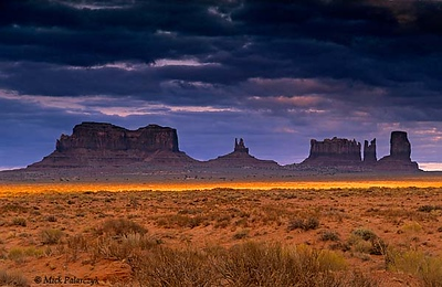 [USA.UTAH 28261 'Sunset at Monument Valley.'  A last ray of sunlight illuminates the plain at Monument Valley. Soft shales at the base of the buttes crumble under the influence of water and frost erosion, undermining the more resistant overlying sandstone which forms vertical cliffs when it collapses. The shales and sandstone date from the Permian period. Photo Mick Palarczyk.