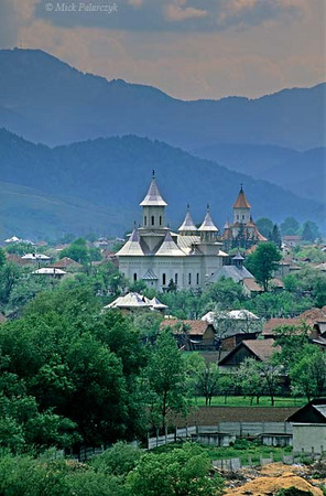 [ROMANIA.MOLDAVIA 23.979] 'Carpathian village.'	 Behind the shining church towers of Vama shimmer the blue mountains of the Carpathians. Photo Mick Palarczyk.