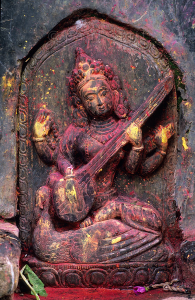 [NEPAL.KATHMANDUVALLEY 27372] 'Saraswati, goddess of learning.'  Relief of Saraswati, the Goddess of Learning, at a small temple near Lele, south of Patan. All those who worship her are believed to receive wisdom and learning. As goddess of music and poetry she is revered alike by Hindus and Buddhist. She is holding  and playing Bina with her two hands and in her other left hand she holds a copy of the vedas. Her mount is a peacock. Yellow and red powder has been smeared on the sculpture during puja offerings. Photo Paul Smit.