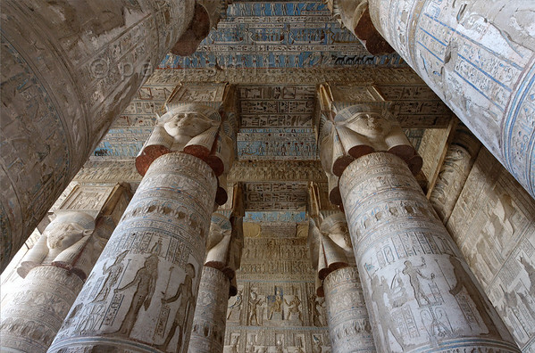 """[EGYPT 29521] 'Outer hypostyle hall of Hathor Temple at Dendera.'  The columns in the outer hypostyle hall (or pronaos) of the Hathor Temple at Dendera are crowned by four-sided capitals carved with the face of the cow-eared goddess. The faces symbolize the four cardinal points of the universe and stress the universal character of the sky goddess Hathor, who was also called """"Lady with the four Faces"""". Here we are looking towards the eastern end of the hall. The ceiling has recently been cleaned of soot and dust and is decorated with a complex set of astronomical figures, constellations, planets and a zodiac. This part of the Dendera Temple was built during the Roman period (first century AD). Photo Paul Smit."""