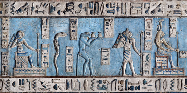 [EGYPT 29577] 'Lions, snakes and a cat on astronomical ceiling at Dendera.'  Snakes and lions in all kind of forms populate the astronomical ceiling in the outer hypostyle hall of the Hathor Temple at Dendera. The ceiling consists of seven separate strips but here we are looking at a detail of the upper register of the SECOND STRIP WEST from centre. The figures in this picture represent decans. Decans were essentially 36 stars or star groups near the ecliptic  whose rise or transit could be used to tell the time during the night. Eventually they were also used by astronomers as place-markers in the sky to divide up the Ecliptic in equal portions. Decans first appear during the Middle Kingdom on the inside of coffin lids, providing the deceased with his own private start clock. Unfortunately, during the subsequent centuries many different lists of decanal stars were developed and very few of these stars can be identified on a modern star map. The decans in this register were listed by Neugebauer and Parker as belonging to the Seti I B decan family. A peculiarity of these decans is that each is associated with a certain mineral, metal or type of wood. It is mentioned in a little caption near the lower part of each figure. Thus the lion-headed seated goddess on the left represents decan number 10 and is paired off with glass and gold. The erect snake next to her is decan no. 9 and is associated with iron and gold. The snake-headed baboon, no.8, is coupled with turquoise. The cat-headed god, no. 7a, is watching over copper and gold. And the lion-headed seated goddess, no. 7 is associated with gold.  For other decanal stars in this register see picture 29572 and 29573. This part of the Dendera Temple was built during the Roman period (first century AD). Photo Paul Smit.