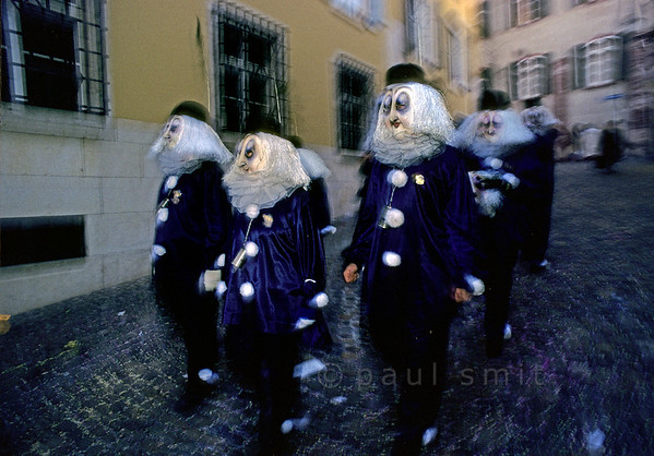 [SWITZER.JURA 6323] 'Clique at dusk.'  During large parts of the Basler Fasnacht (carnival of Basel) the streets are occupied by Cliques (groups or bands). This beautiful ensemble is photographed before sunrise after Morgestraich, the start of the carnival at 4 a.m. on Monday. Photo Paul Smit.