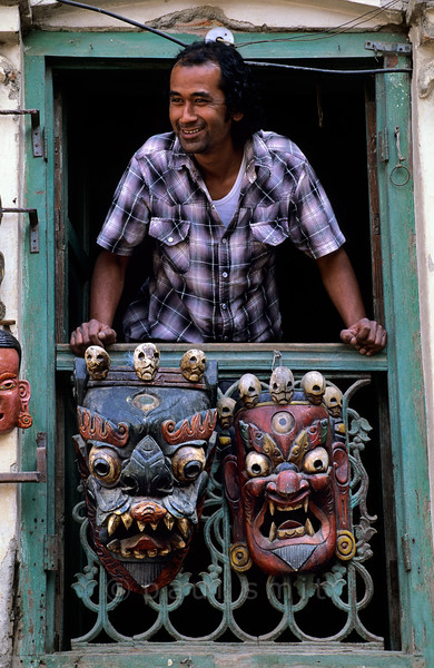 [NEPAL.KATHMANDUVALLEY 27266] 'Mask shop at Kathmandu's Durbar Square.'  The owner of a mask shop at Kathmandu's Durbar Square is looking from a window which is decorated with masks of Bhairava. The fierce looking Bhairava, god of annihilation and the march of time, is a popular subject for masks. He is thought to preside over cremation grounds, hence the garland of skulls around his head. Photo Paul Smit.