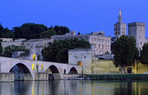 """[FRANCE.PROVENCE 10930] 'Sous le Pont d'Avignon.'  Of course the famous song goes like this: """"sur le pont . . ."""" But that doesn't tally with the historical facts. People didn't dance on the bridge but on the bank of the river in the shade of the arches. The nicest view of the famous bridge and the walled town of Avignon with its papal palace can be enjoyed from the opposite bank of the river. To get there you have to use a little ferry because the bridge was partly devoured by the Rhône during a catastrophic flood in 1669. Photo Paul Smit."""