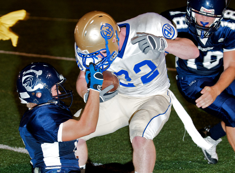 Image © 2008 Ralph Mawyer, Jr.   Boerne-Champion defender caught in illegal facemask tackle of Alamo Heights running back, 3 Oct 2010, Boerne, Texas.