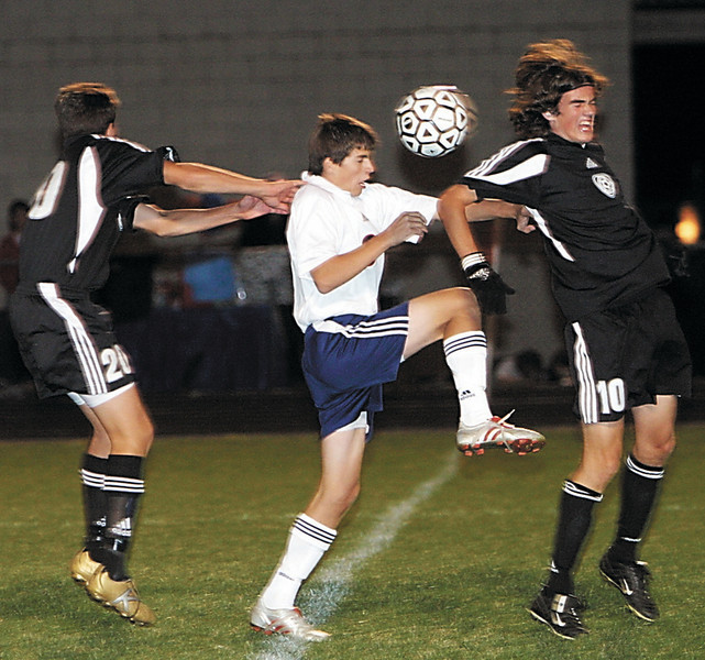 Matt Stokes, middle, of Grove City heads the ball past Jason Murray, right, and #20 of Westerville Central during last night's league championship match at Grove City.
