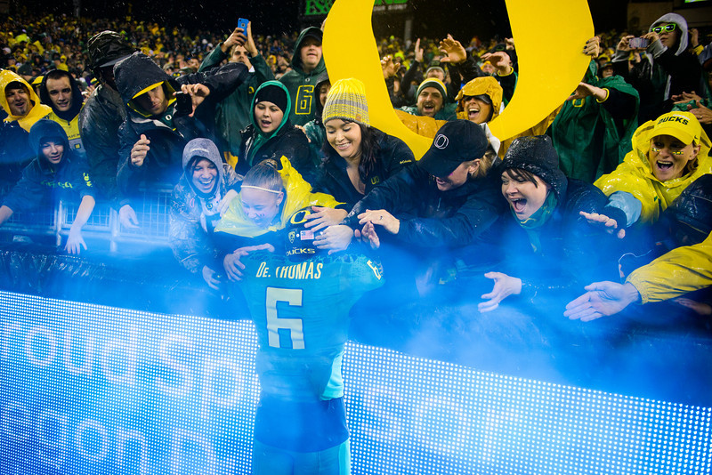 Oregon junior running back De'Anthony Thomas (6) is mobbed by a group of Duck fans in the North end zone, in what has become a tradition for the season. The No. 2 Oregon Ducks play the California Golden Bears at Autzen Stadium in Eugene, Ore. on Sept. 28, 2013.