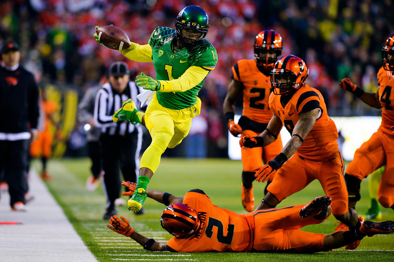 Oregon senior wide receiver Josh Huff (1) leaps over Oregon State junior cornerback Steven Nelson (2) during the first quarter. The No. 13 Oregon Ducks play the Oregon St. Beavers at Autzen Stadium in Eugene, Ore. on Nov. 29, 2013.