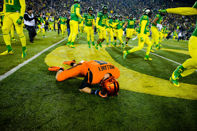 Oregon State sophomore wide receiver Richard Mullaney (8) lies injured on the 50-yard line as the field is swarmed by jubilant Ducks and fans alike. The No. 13 Oregon Ducks play the Oregon St. Beavers at Autzen Stadium in Eugene, Ore. on Nov. 29, 2013.