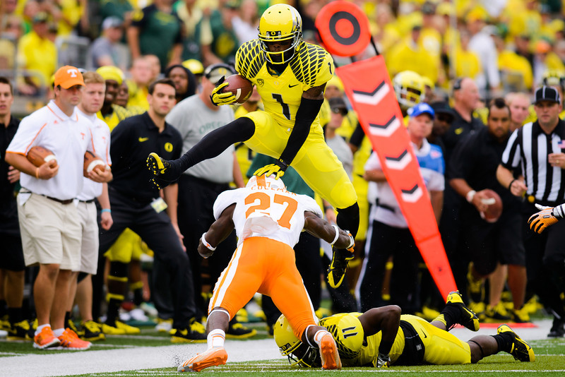 Oregon senior wide receiver Josh Huff (1) hurdles Tennessee junior defensive back Justin Coleman (27) as Huff makes his way down the sideline. The No. 2 Oregon Ducks play the Tennessee Volunteers at Autzen Stadium in Eugene, Ore. on Sept. 14, 2013.