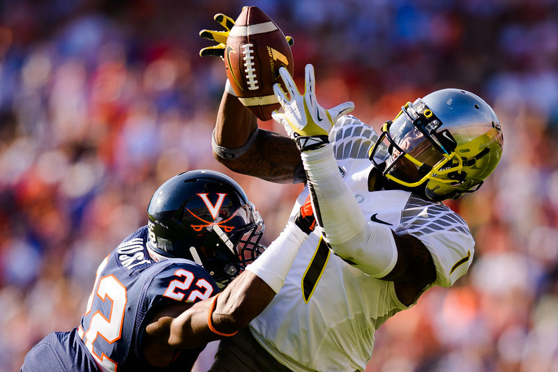 Oregon's Josh Huff (#1) secures an end zone pass under heavy pressure from Cavaliers tailback Khalek Shepherd (#23), scoring a touchdown during the second quarter. The No. 2 Oregon Ducks face the University of Virginia Cavaliers at Scott Stadium in Charlottesville, Vt. on Sept. 7, 2013.