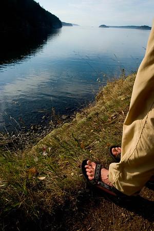 Person in sandals next to shoreline, Cypress Island, WA USA