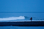 Surfer holding surfboard by wave, WA USA