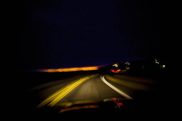Blurred driver's view of two lane highway, WA USA