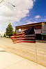 US flag reflected in window in small town, Sprague, WA USA