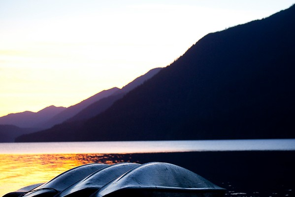 Canoes stacked in row at sunset, Lake Crescent, Olympic National Park, WA USA