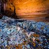 Fremont anthropomorphs in shelter behind lichen-covered rock, Utah