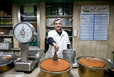 A sweet shop owner proudly poses with the delicacies at his store in Tripoli, Lebanon.