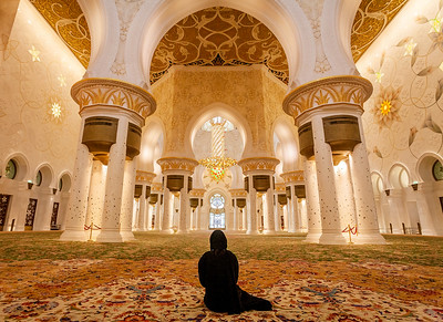 A woman sits in the Sheik Zayed Mosque, Abu Dhabi, the United Arab Emirates, 2010