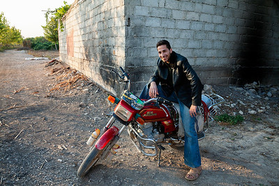 A villager poses with his soon-to-be-outlawed motorbike in Bait Sawa, Syria, 2008