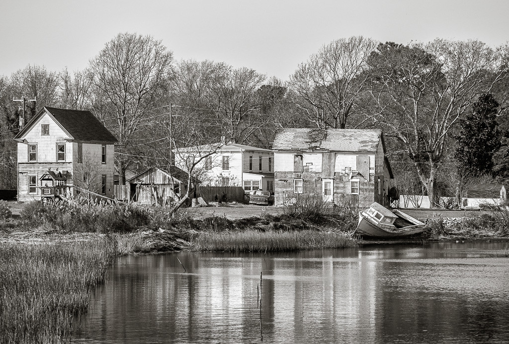 A derelict boat sits aground behind old, run down houses in the small fishing community of Oyster on Virginia's Eastern Shore.
