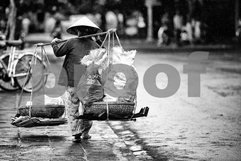Old woman under the rain in Hoi An, Vietnam