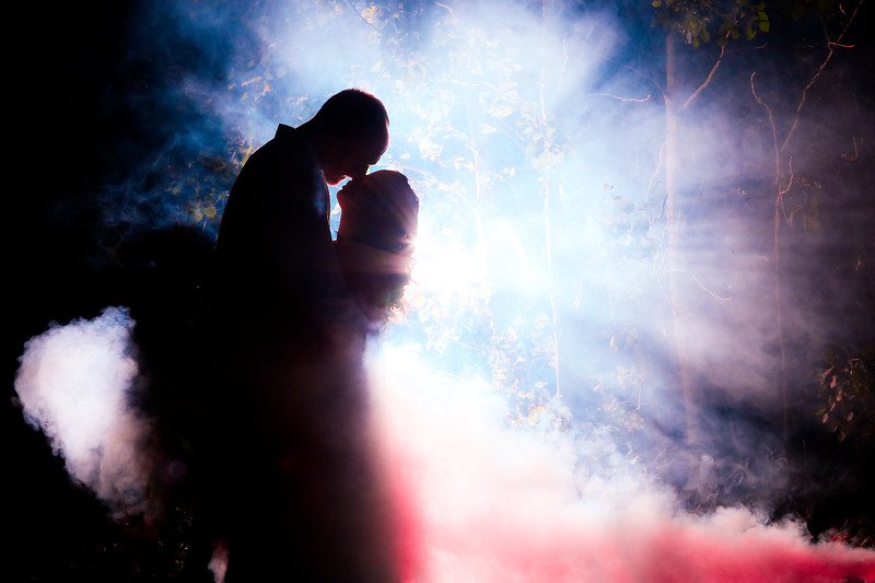 Film-noir inspired. Dramatic backlighting and mysterious fog, coupled with rays of light... Did I mention there is a lovely couple Eskimo kissing in the foreground?