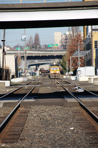 Union Pacific train heading through south east Portland. It was amazing how much foot traffic traversed the tracks in this industrial area. In the background one can see the Portland & Western local pulling onto the other mainline track.