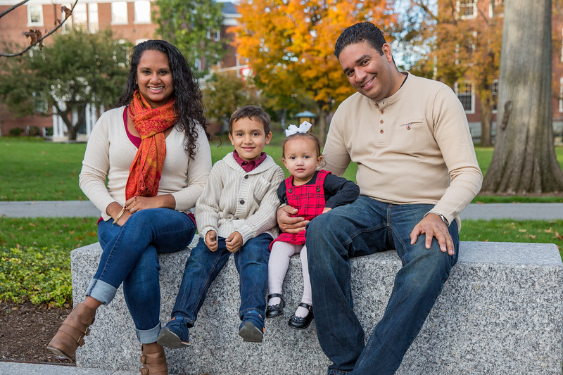 Family posing for a portrait including fall foliage on a college campus