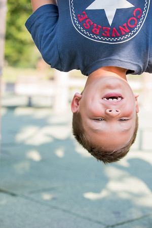 A boy hangs upside-down during a family photo shoot