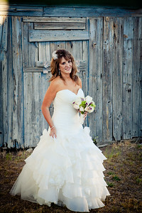 Bride in front of barn, M Charlotte Photo