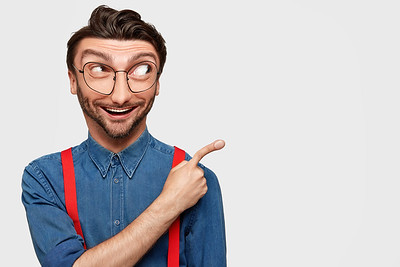 Recommend you to use this copy space. Cheerful young bearded male with trendy hairdo and positive smile, dressed in casual clothes, points left against white studio background, expresses cheer