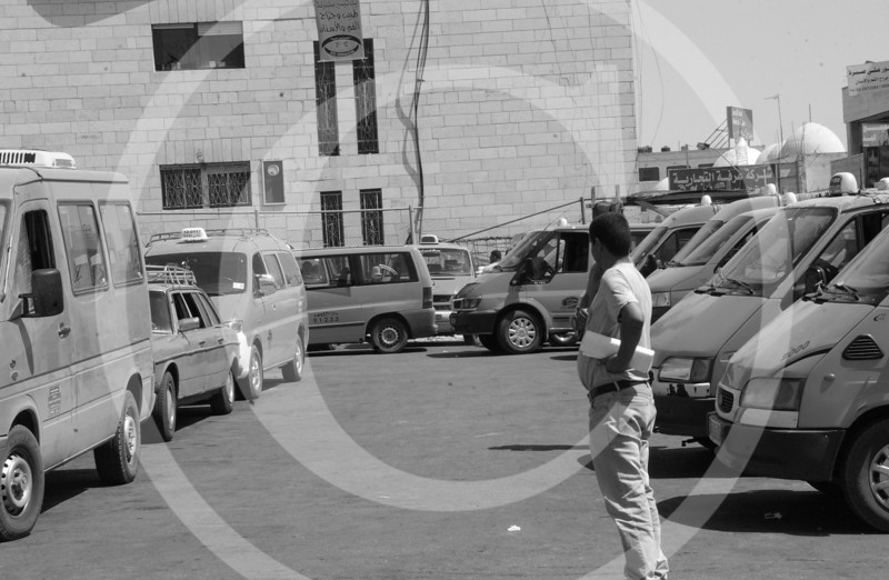 A man looking over the taxis waiting in line in Ramallah.