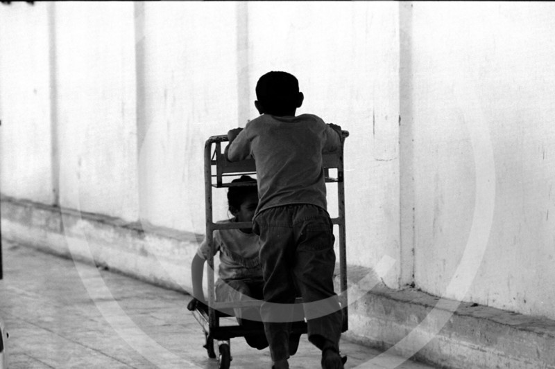 A boy pushing a girl on a luggage cart in Jericho, Israel/West Bank while they are stuck at the border in between Jordan and Jericho.  The families sleep at the checkpoint for days waiting for permission to cross over from the Israelis.