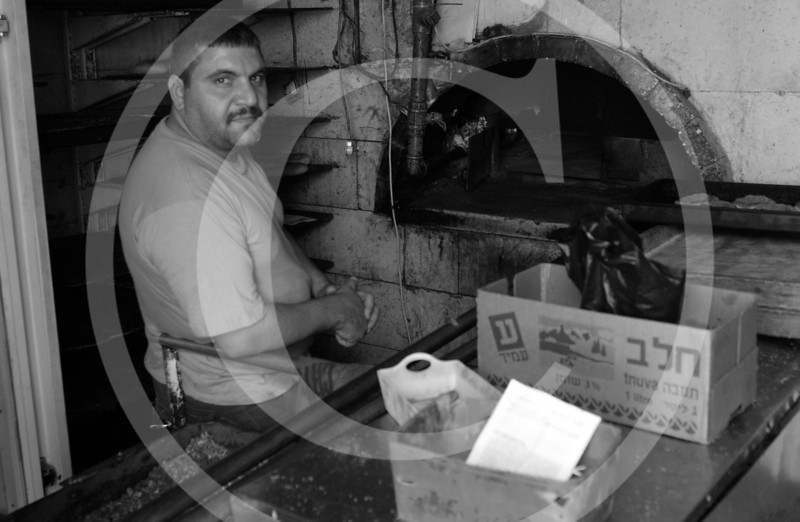 A pizza baker stands in front of his oven in Hebron, West Bank.  Business is slow, but its enough to keep going.