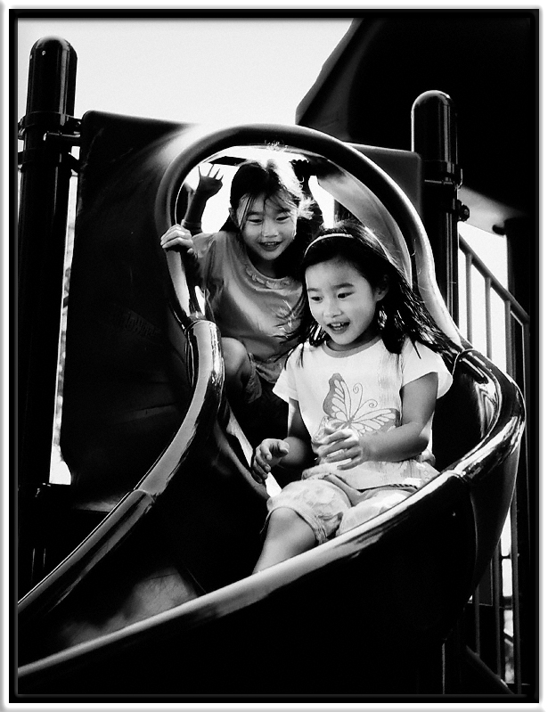 Twins & Slide  Julianne & Mike's identical twins, Anastasia & Priscilla, love taking rides together down the big slide.  (Little brother Evan is not far behind them.)  Cuesta Park Mountain View, California  12-SEP-2010