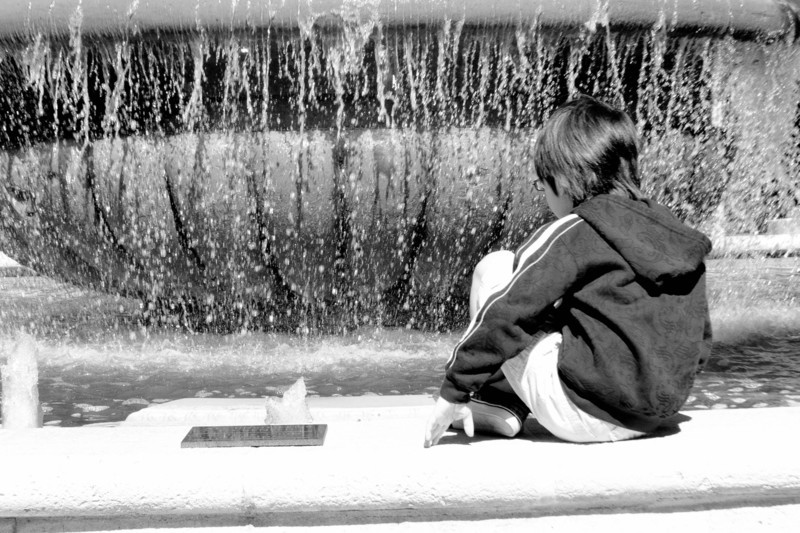 Boy sitting at fountain