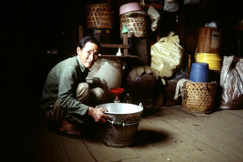 Taiwan, Farm near Ali Shan, The Plum Wine Farmer pouring wine for a visitor