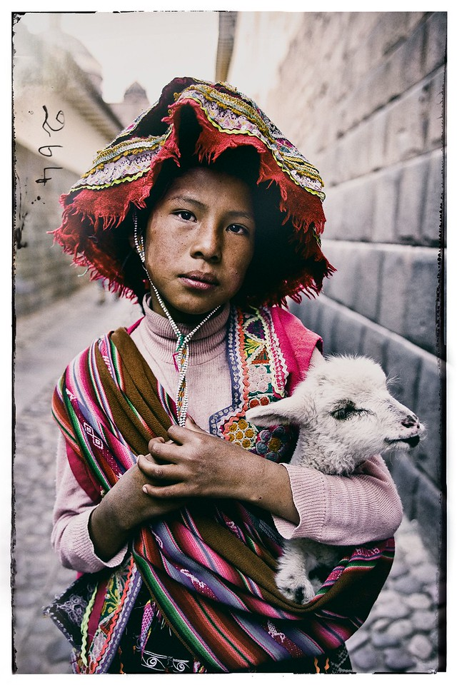 A Quechua girl dressed in traditional clothing holds her baby llama in Cuzco, Peru.