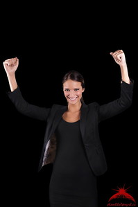 Excited Executive Woman in Suit with Raised Hands Smiling