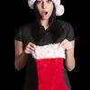 Woman In Santa Hat Holding a Christmas Sock