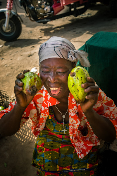 A market seller at the Dome Market holds her produce with joy. There is a strong sense of community among market sellers at any of the markets in Ghana.
