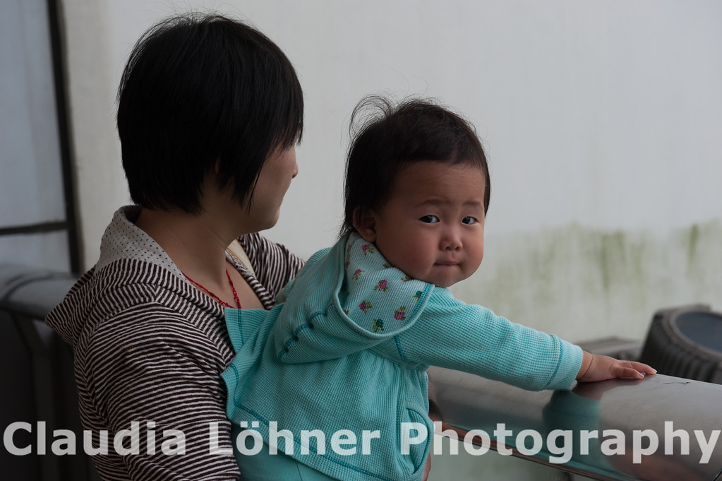 This is one of my favorite snapshots : while the mother gazes down at the city of HongKong ( misty as it often will be ), the baby is looking directly at me .